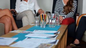 Ett bord med vattenglas, en vattenkanna och en bunt pennor. I bakgrunden syns fyra personer som diskuterar med varandra.