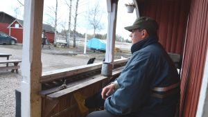 Man sitter på bänk på terass och tittar utåt mot gården.