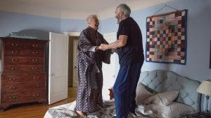 Joan (Glenn Close) och Joe (Jonathan Pryce) håller varandra i händerna och hoppar på sängen av glädje.