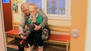 Sari Reinikainen riisuu 2-vuotiaan Nestori-poikansa ulkovaatteita Sulkavan Päiväkoti Touhulassa.