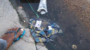 Kalsarit lätäkössä muovijätteen kanssa Maputon kadulla Mosambikissa.