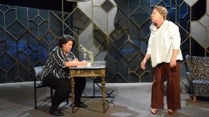 Två kvinnor på teaterscen. En sitter och skriver i ett block, till höger står en annan kvinna.