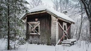 Autiotalo, laudat ikkunoissa, lunta katolla ja maassa.