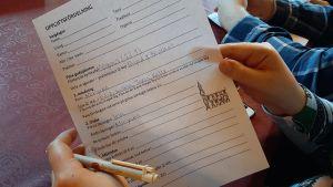 Två händer håller i ett papper med uppgiftsfördelning för en gudstjänst, vem som förbereder kyrkkaffet, vem som tänder ljus och vem som läser texter.