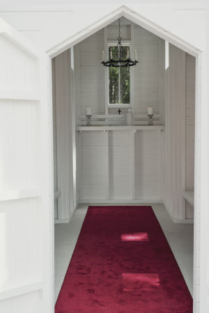 Pieni kirkko sisältä: Punainen matto johtaa ovelta alttarille; sivuilla yhdet penkit, katosta roikkuu musta takorautainen kynttelikkö.
