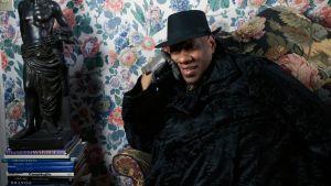 Muotitoimittaja André Leon Talley istuu mustassa viitassa kukikkaan tapetin peittämän seinän edessä. Kuva dokumenttielokuvasta.