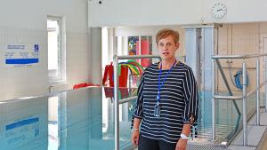 Anne står vid simbassängen, där vattenytan är stilla och ljusblåskiftande.