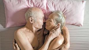 Vanha mies ja nainen makaavat sylikkäin sängyssä.