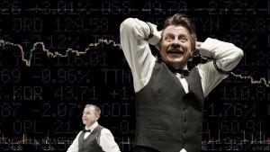 En man i vit skjorta och väst står och håller händerna bakom huvudet och grinar. I bakgrunden syns ett stort diagram med börskurser.