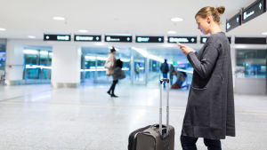 Kvinna på flygfält som petar på sin telefon.