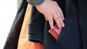Hand sträcker sig efter plånbok