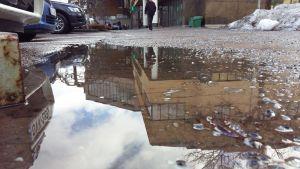 Pargas stadshus speglas i en vattenpöl.