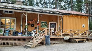 Ett gult trähus med julbelysning. På väggen finns en stor grönvit skylt där det står byaboden.