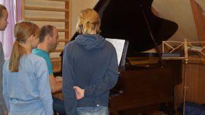 Barn runt  ett piano/en flygel. En man sitter och spelar.