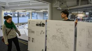 En kvinna tittar på tre stora planscher med ritningar som en man står bakom och håller upp.