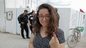 Väljare i Tunis visar sitt finger som markerats med bläck som bevis på att hon röstat i lokalvalet.