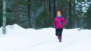 En kvinna springer i skogen genom snön, hon har färggranna yllesockor på fötterna.