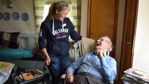Erika Wikström står bredvid 91-årige Harry som sitter i sin gungstol. Båda ser på varandra och ser glada ut.