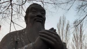 Övre delen av Konfuciusstaty, står med händerna ihop, blickar ut