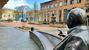 En staty i Ülemiste City i Tallinn där en man lyfter sitt finger i riktning mot några gamla byggnader längre bort.