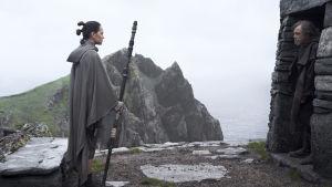 Rey (Daisy Ridley) står utanför ett stenhus och ser på Luke Skywalker (Mark Hamill) som står i dörröppningen och inte vill umgås.