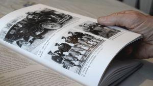 En hand som håller i en sida i boken Det sista brukssamhället.
