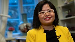 Julie Chen, skrattar, bakåtlutad i granngul kavaj, mörk pagefrisyr, i arbetsrummet