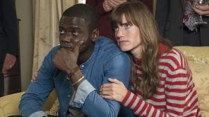Chris (Daniel Kaluuya) sitter tillsammans med Rose (Allison Williams) i en soffa och ser bekymrade ut.