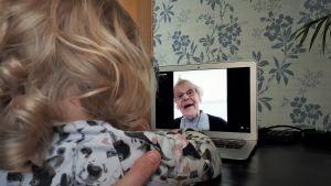 Ett barn med lockigt hår ser på en dataskärm med en bild på en äldre kvinna som ler.