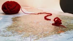 Finlands karta och ett frågetecken i röd ylletråd.