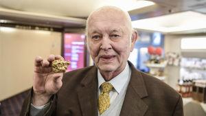 Antti Aarnio-Wihuri håller den största guldklimpen som hittats i Finland i handen.