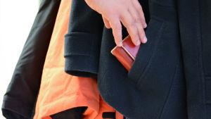 Hand sträcker sig efter plånbok ur ficka