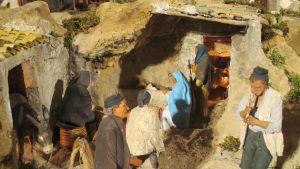 Yksityiskohta pelkistetystä sisilialaisesta jouluseimestä: Pyhä perhe savimajassa, ympärillä aasi, kyläläisiä ja pillipiipari.