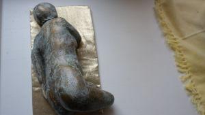 En liten skulptur med en liggande person.