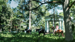 Tre hästekipage rider genom skog, förbi ett lusthus i 1800-talsstil.