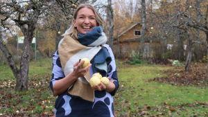 Elise Hindström under äppelträd med äpplen i händerna.