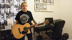 Tom Håkans står inomhus med gitarr i handen. I bakgrund finns en dator på ett skrivbord, en synth och på väggen finns tavlor med cd-skivor.
