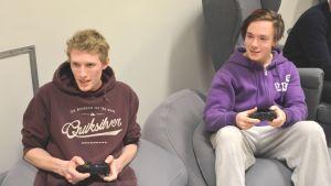 Killarna sitter på soffor och spelar TV-spel.