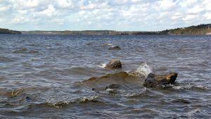 Våg slår över strandsten i Pyhäjärvi.