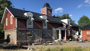 Hotel Nestor i Korpo med röd fasad, vita knutar och sitt höga torn mitt uppe på taket.