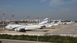 Flygplan med flygbolaget El Als markeringar parkerade på en flygplatsplatta med en rad vita höghus i bakgrunden.