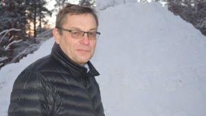 En man står ute iklädd vinterjacka. Bakom en stor snöhög.