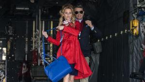 Gail (Elizabeth Banks) går ut från ett flygplan, tätt bakom henne kommer John (John Michael Higgins).