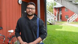 ung man framför faluröda hus