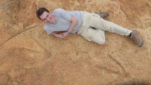 Tretåigt dinosauriefotspår i sten, bredvid ligger en glad man och poserar.
