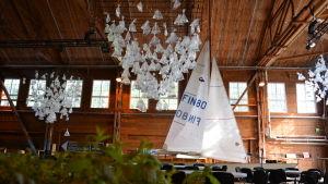 En stor festsal med en segelbåt med hissade segel. I taket hänger konstverk som ser ut som mängder av små segelbåtar.