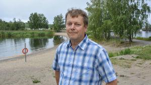Esa Hirvijärvi, miljöinspektör vid Vasa stad, står vid badstranden på Smulterö.