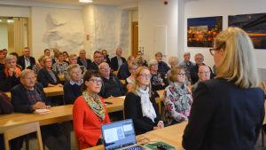 folk lyssnar uppmärksamt på ett föredrag