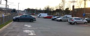 Personbilar som står parkerade på en affärs parkering. Till vänster syns järnväg. Andra affärer och hus i Karis centrum syns i bakgrunden. Den nya järnvägsbron syns också i bakgrunden. Kväll, solnedgång. Vår.
