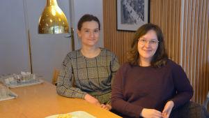 Två kvinnor sitter bredvid varann vid ett matbord.